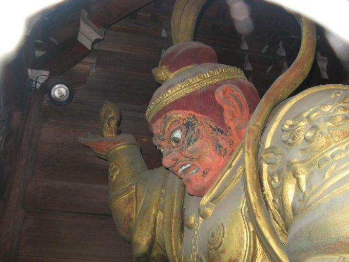 薬王院の門にある赤い顔の像